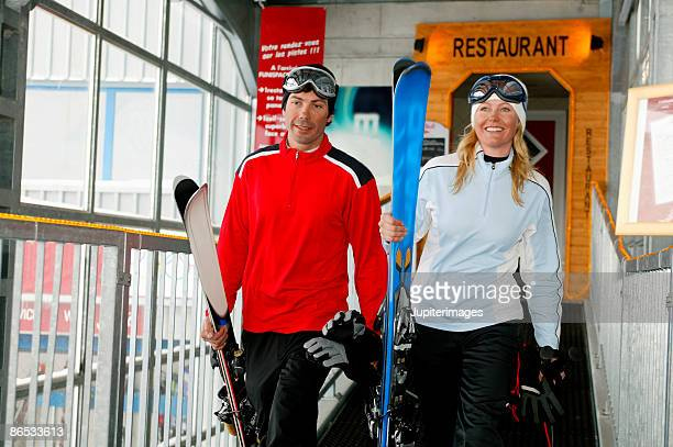 Couple carrying ski equipment