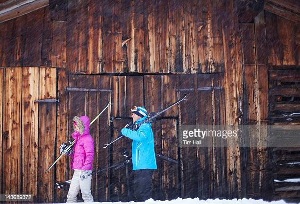 couple carrying skis and poles in snow - lech stock photos and pictures