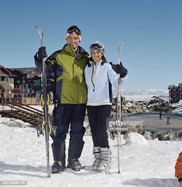 Couple carrying skis in ski field, smiling, portrait