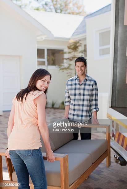 Paar tragen sofa aus Möbelwagen in neues Haus