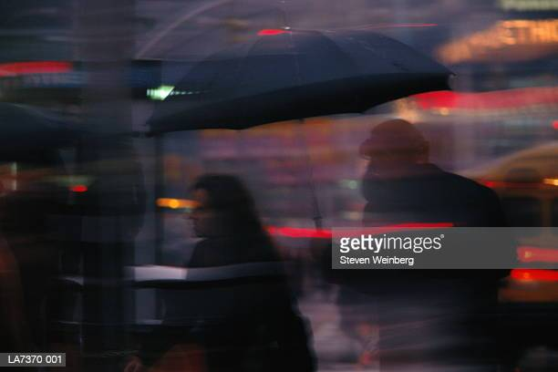 Couple carrying umbrella, walking along street, night (long exposure)