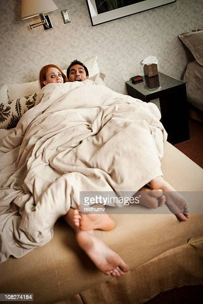 Couple caught in bed with feet hanging out the covers