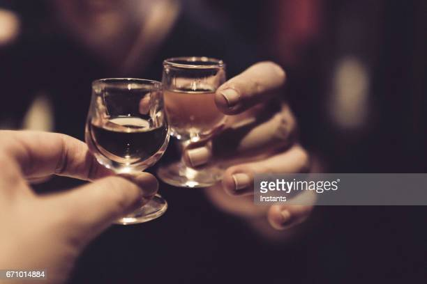 Couple celebrating and cheering on good news after a meal, with each a snifter of almond liqueur in their hands.