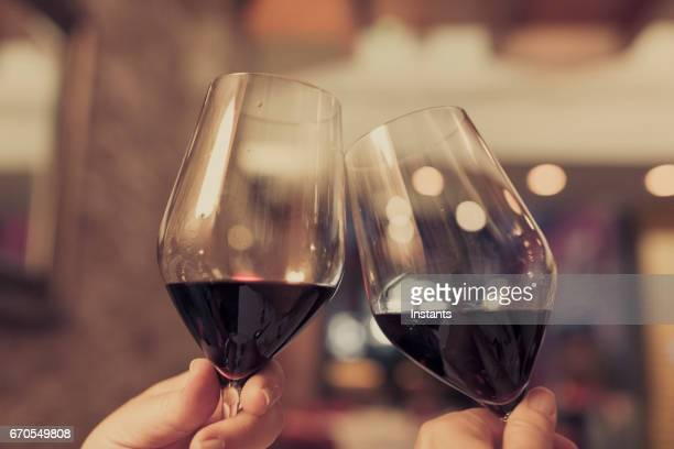 Couple celebrating and cheering on good news, with each a glass of red wine in their hands.