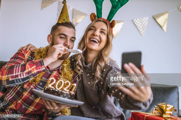couple celebrating christmas at home, holding chocolate cake with lit candles shaped as numbers 2021 and having a video call with friends - new year's eve stock pictures, royalty-free photos & images