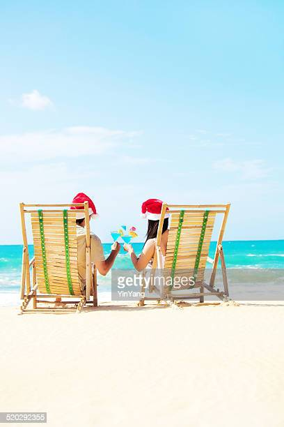 couple celebrating christmas vacation on beach with tropical drinks - hawaii christmas stock pictures, royalty-free photos & images
