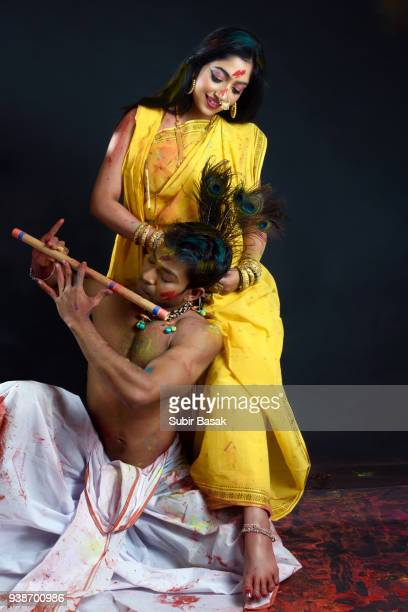 Couple celebrating holi and playing flute.