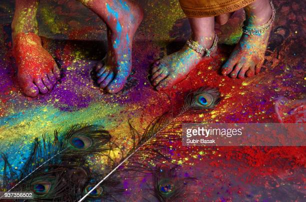 Couple celebrating Holi with colors and musical intruments.