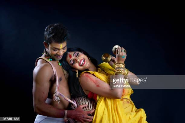 Couple celebrating Holi with colors and traditional musical instruments.