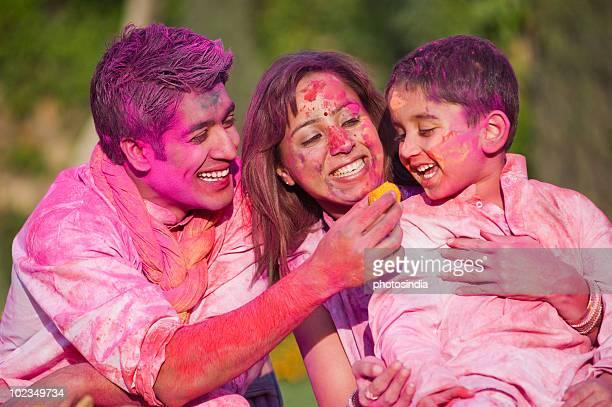 couple celebrating holi with their son - mom flirting 個照片及圖片檔
