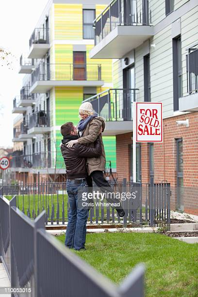 Couple celebrating in front of apartment