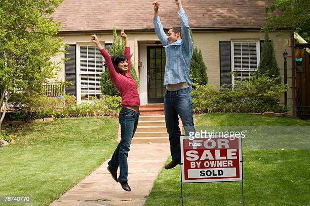 Couple Celebrating in Front of New House