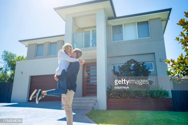 couple celebrating in front of their new home. - in front of stock pictures, royalty-free photos & images