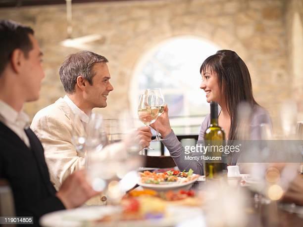 couple celebrating in restaurant - monty rakusen stock pictures, royalty-free photos & images