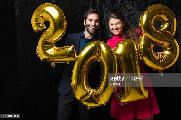 Couple Celebrating New Year's Eve with 2018  balloons