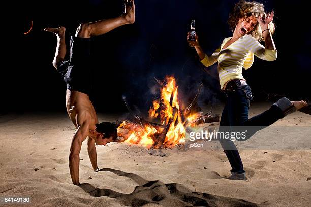 Couple celebrating on beach with bonfire