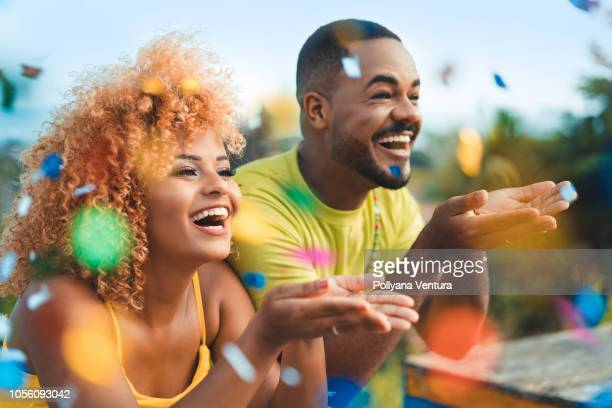 couple celebrating with confetti - carnival stock photos and pictures