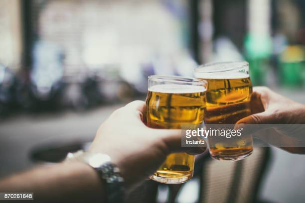 Couple celebrating with two glasses of beer on a Parisian cafe-bar table.