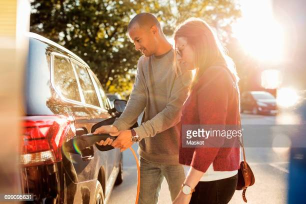 couple charging electric car at station on sunny day - electric vehicle charging station stock photos and pictures