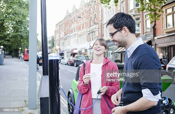 Couple charging electric car on street