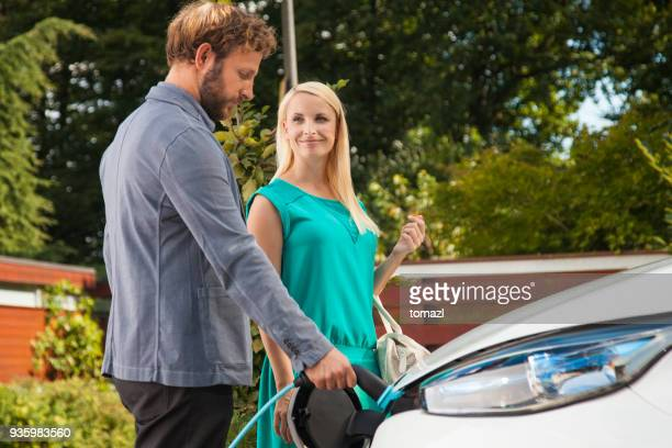 couple charging the car before going to work - hybrid car stock photos and pictures