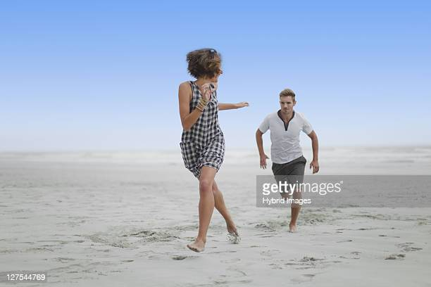 couple chasing each other on beach - chasing stock pictures, royalty-free photos & images
