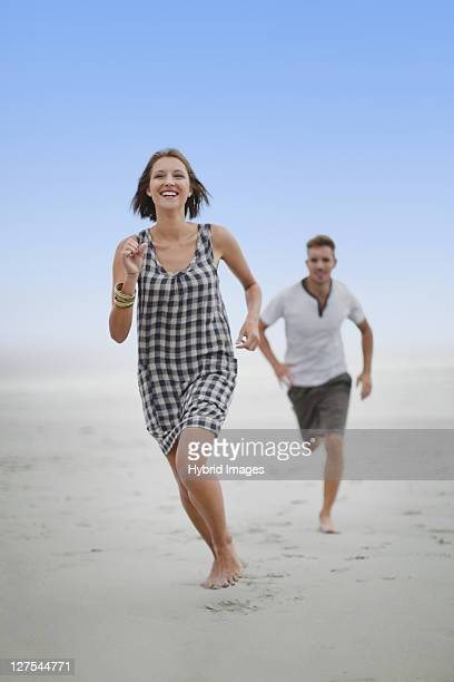 Couple chasing each other on beach