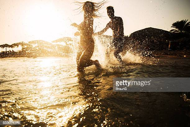 Couple chasing in the sea at sunset.