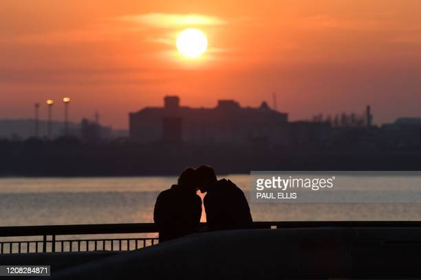 A couple chat as the sun sets on Liverpool Pier Head in Liverpool northwest England on March 26 2020
