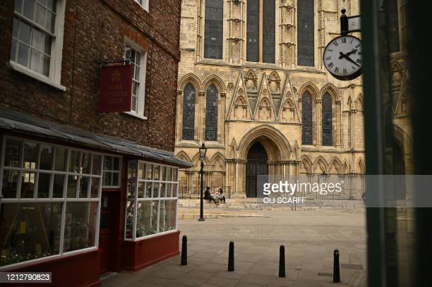 Couple chat as they sit on the steps outside York Minster in York, northern England on May 12 during the nationwide lockdown due to the novel...