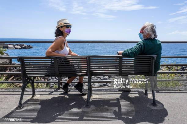 A couple chat at a distance while wearing gloves and masks while sitting on a bench in the sun in front of the sea in the small port of San Giovanni...