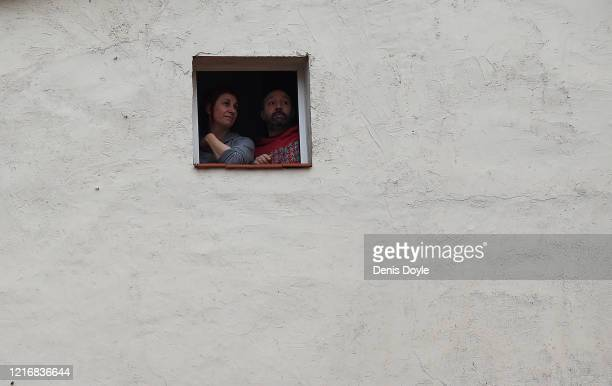 Couple chat with neighbours from their window on April 04, 2020 in Madrid, Spain. Spain ordered all non-essential workers to stay home for until...