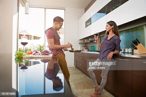 Couple chatting and drinking wine whilst cooking in kitchen
