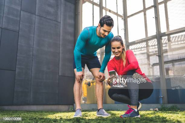 couple checking at their workout performance on phone app - checking sports stock pictures, royalty-free photos & images