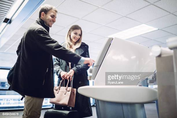 Couple Checking In at Airport Terminal
