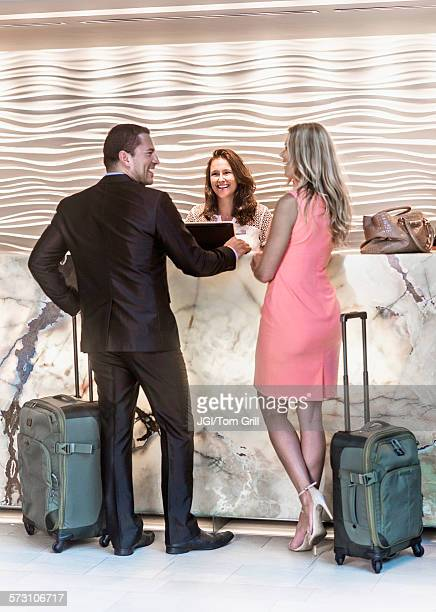 Couple checking into hotel at counter