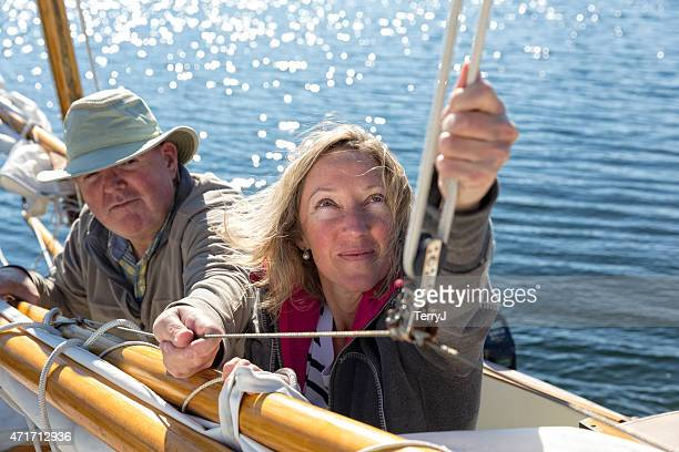 couple checks lines on sailboat - sail boom stock pictures, royalty-free photos & images