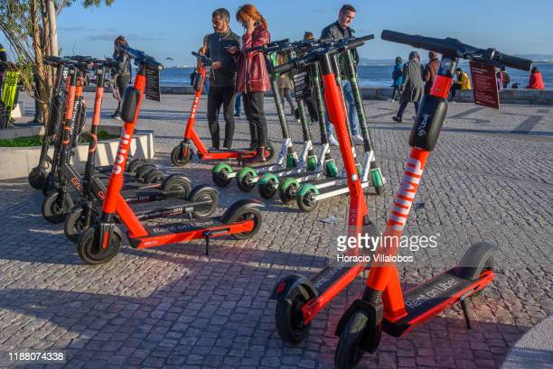 Couple checks on a Jump-Uber e-scooter parked in Cais do Sodre, by the Tagus River, on November 16, 2019 in Lisbon, Portugal. Uber has now joined the...
