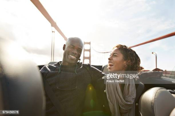 couple cheering and laughing on the backseat of convertible car - progress stock pictures, royalty-free photos & images