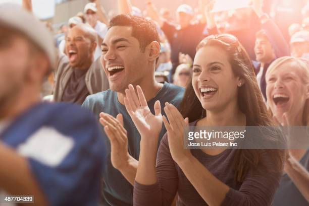couple cheering at sporting event - taper dans les mains photos et images de collection