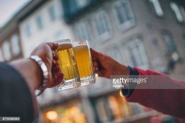 couple cheering on good news with their beer mugs, each containing a different type of beer. - help:ipa stock pictures, royalty-free photos & images