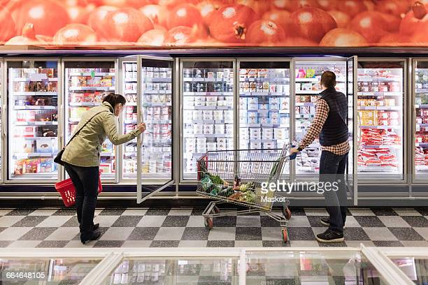 Couple choosing at refrigerated section in supermarket