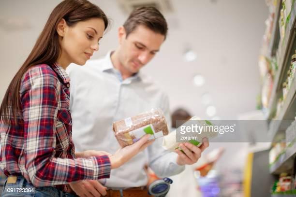 couple choosing between wholegrain and refined rice - cibi e bevande foto e immagini stock