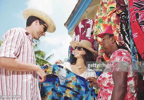Couple choosing brightly patterned shirt at clothes stall
