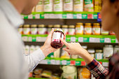 Couple choosing jar of jam