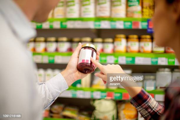 couple choosing jar of jam - for sale stock pictures, royalty-free photos & images