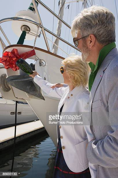 Couple christening boat with bottle of champagne