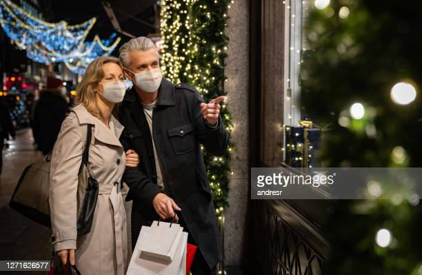 couple christmas shopping wearing a facemask in london - merchandise stock pictures, royalty-free photos & images