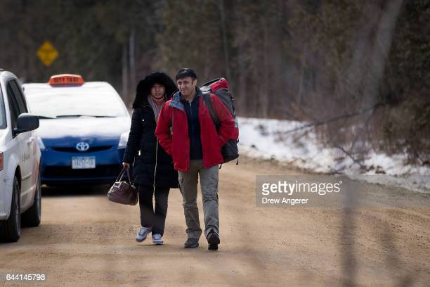 A couple claiming to be from Turkey exit a taxi and prepare to cross the USCanada border into Canada February 23 2017 in Hemmingford Quebec Canada In...