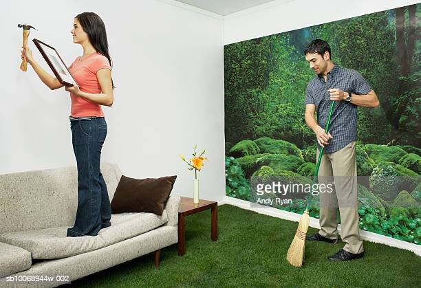 Couple cleaning living room decorated with nature themes